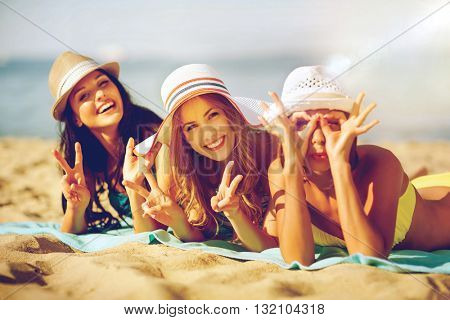summer holidays and vacation - girls sunbathing on the beach