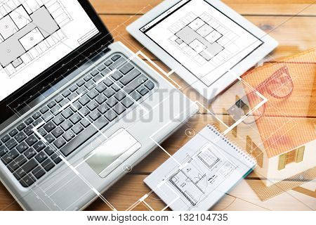 architecture, business and technology concept - close up of on laptop computer, tablet pc, notebook and eyeglasses with blueprint of room on wooden table