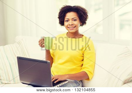 people, technology and leisure concept - happy african american young woman sitting on sofa with laptop computer and drinking tea from cup at home