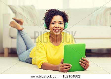 people, technology and leisure concept - happy african american young woman lying on floor with tablet pc computer and headphones listening to music at home