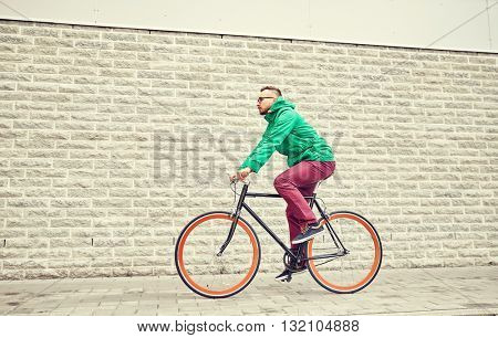 people, style, leisure and lifestyle - young hipster man riding fixed gear bike on city street over brick wall background