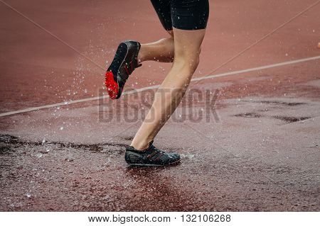 athlete foot men running steeplechase. a spray of water