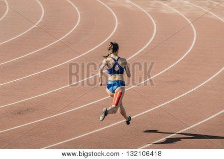 girl sprinter runs through stadium. feet taping