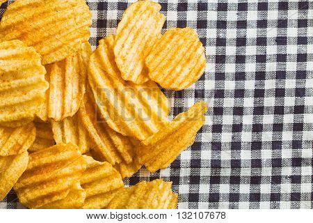 Crinkle cut potato chips on checkered tablecloth. Tasty spicy potato chips.