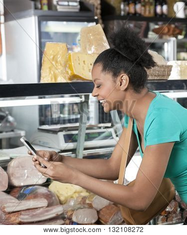 Happy Woman Photographing Through Mobilephone In Cheese Shop