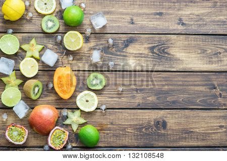 Tropical fruits with cubes of ice making a left border on wooden background with a space for your text