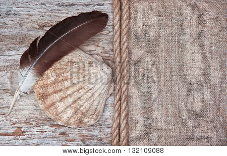 Grunge Background With Big Seashell, Rope And Feather On Sackcloth