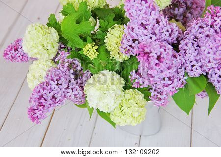 A tender bouquet of lilac and buldenezh, decorative form of Viburnum, in the form of a snow globe on a white wooden table in a silver vase