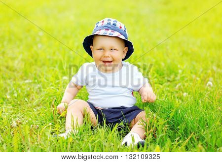 Happy smiling baby sitting on grass in sunny summer day