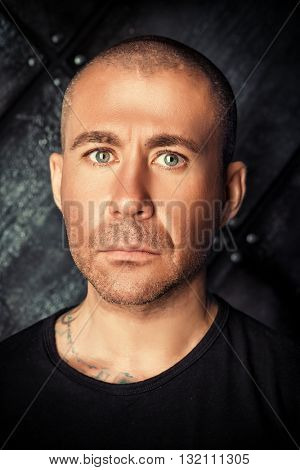 Close-up portrait of a serious man in black clothes over dark grunge background.