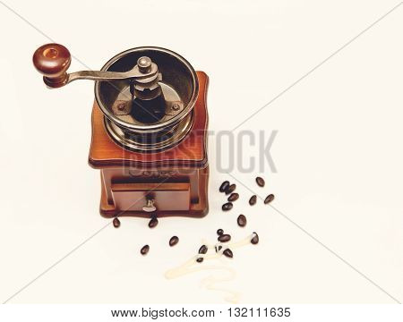 The Vintage Old Stile Wooden Coffee Grinder with Beans of Coffe on the White Background,Top View,Toned
