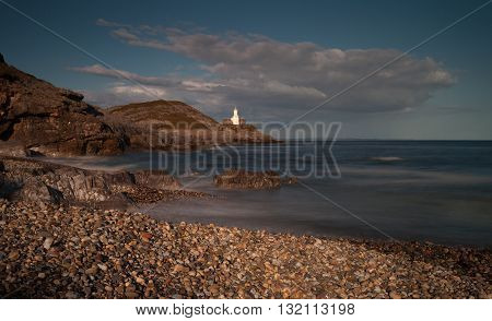 The beach of pebbles, Bracelet Bay, featuring Mumbles Lighthouse in Swansea, South Wales