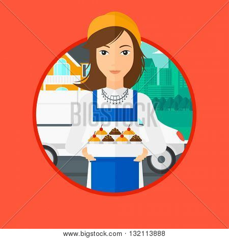 A female baker holding a box of cakes. A baker delivering cakes. Baker with cupcakes standing on the background of delivery truck. Vector flat design illustration in the circle isolated on background.