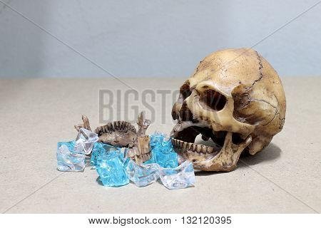 decayed teeth human skull with candy on wood background. like a people eating candy too much. poster