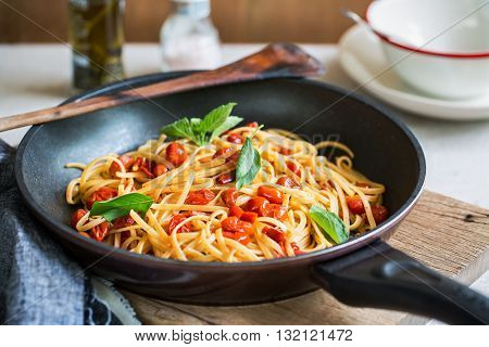 Freshly cooked Fettuccine with cherry tomatoes in a sauce pan