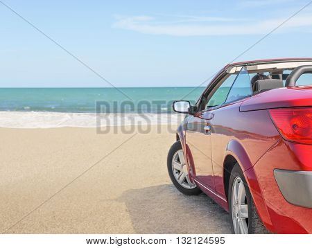 Summer car trip vacation . Woman in red car at background of sea water. Travel , freedom and holidays concept.