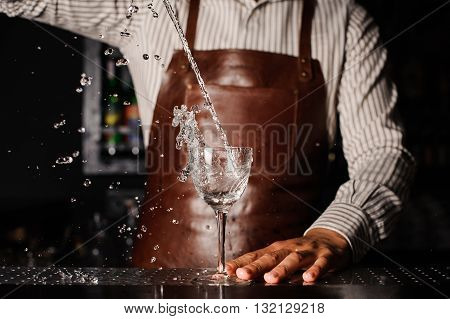 Water splashes out of the glass infront of barman