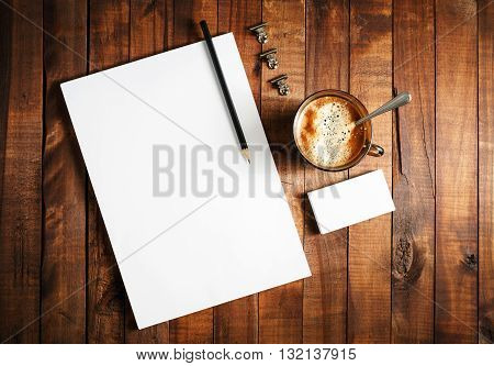 Blank branding template. Photo of blank stationery set on vintage wooden table background. Letterhead cup of coffee business cards and pencil. Blank branding template. Corporate identity mock-up. Top view.