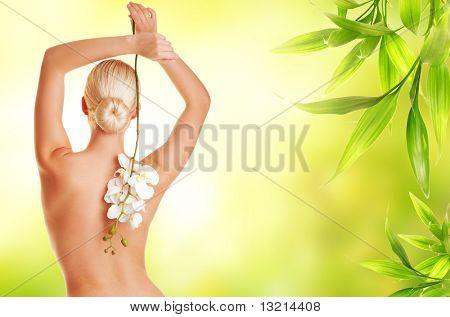 Mulher loira linda com a flor da orquídea