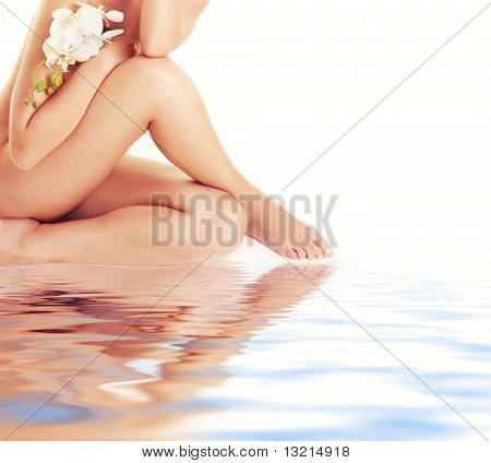 Female legs with white orchid