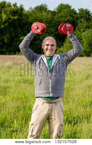 Man Holding Red Dumbbells In The Air
