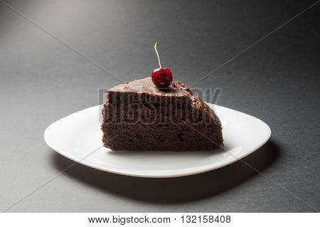 Slice of delicious chocolate cake with cherry on top on a white plate on a dark background.