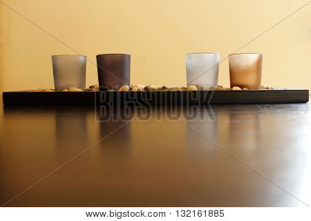 Four Unlit Candles On Stones On A Wood Surface