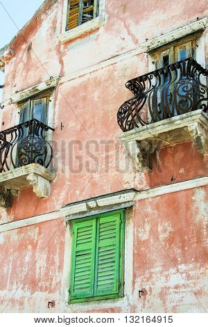 Vintage pink buiding with green wooden shutters in Dubrovnik Croatia