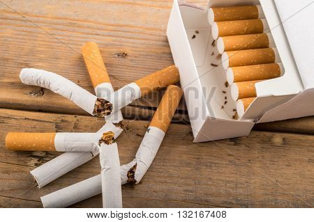 Quit Smoking - Broken Unsmoked Cigarettes Next To A Plain White Pack