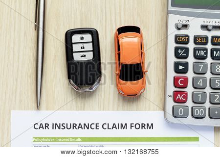 Top view of car insurance claim form with car key and car toy on wooden desk.