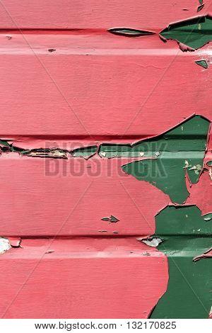 Peeling red and green paint on a metal garage door
