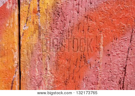 A vibrant background texture of crackled wooden boards with strokes of yellow pink and red paint; an abstract texture