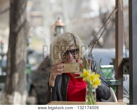 Beautiful blondie girl  is smiling while making photo on the phone