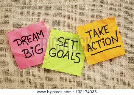 dream big, set goals, take action - motivational advice or reminder on sticky notes against canvas