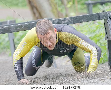 STOCKHOLM SWEDEN - MAY 14 2016: Smiling struggling man crawling under bars in the obstacle race Tough Viking Event in Sweden May 14 2016