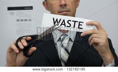 Male office worker or businessman in a suit and tie cuts a piece of paper with the word waste on it as a waste reduction business concept.