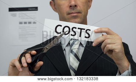 Male office worker or businessman in a suit and tie cuts a piece of paper with the word costs on it as a cost reduction business concept.
