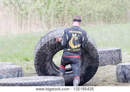STOCKHOLM SWEDEN - MAY 14 2016: Rear view of man struggling to tip a large tractor tire obstacle in the obstacle race Tough Viking Event in Sweden April 14 2016