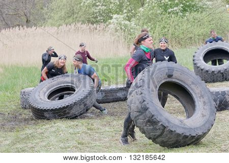 STOCKHOLM SWEDEN - MAY 14 2016: Group of men and woman struggling to tip a large tractor tire obstacle in the obstacle race Tough Viking Event in Sweden May 14 2016