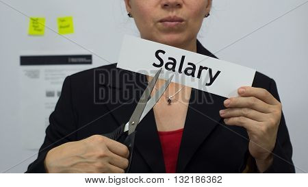Female office worker or business woman cuts a piece of paper with the word salary on it as a salary or pay reduction business concept.