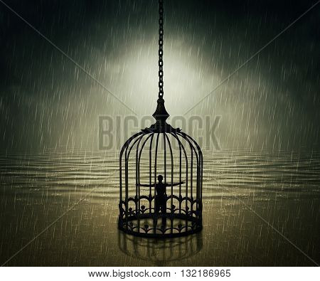 Man standing closed in a bird cage with wide opened hands in front of the ocean horizon in a rainy day. Life limitation trapped in a prison concept
