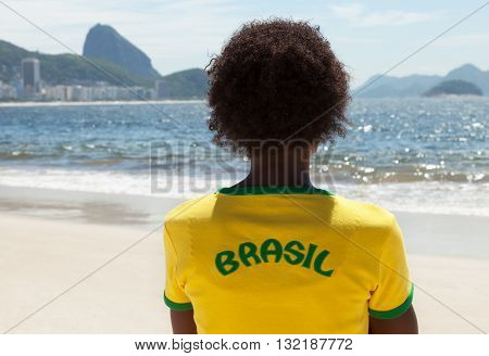 Woman in brazilian jersey looking at Sugarloaf mountain at Rio de Janeiro