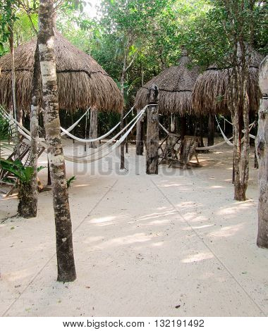 Thatched Tiki Huts, woven hammocks, and chairs for resting and relaxing