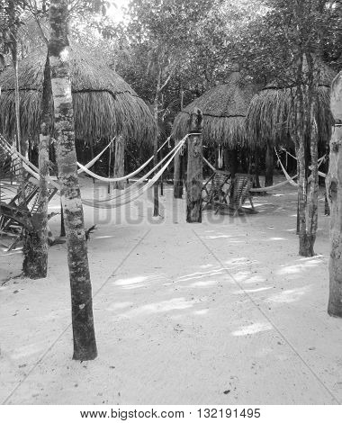 Thatched Tiki Huts, woven hammocks, and chairs for resting and relaxing in the sand