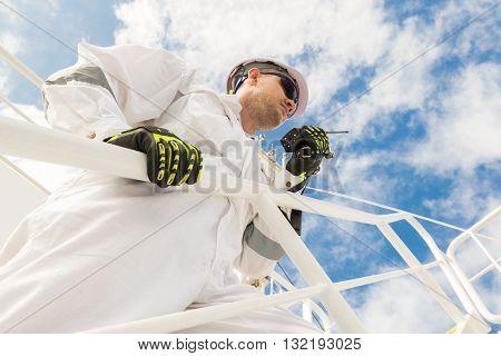 Engineer in white workwear speaking by VHF