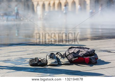 Family Shoes and a backpack left near the mirror fountain in Bordeaux France