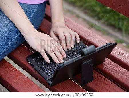 Woman's hands on a keyboard she is working outdoors on the bench
