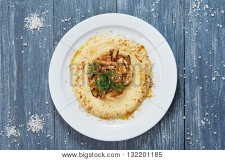 Hummus plate with copyspace. Hummus spread from chickpeas with veal stew. Hummus with meat. Arabic, jewish, eastern restaurant traditional food top view, flat lay at rustic blue wood background.