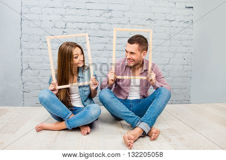 Portrait Of Happy Smiling Man And Woman Posing Inside Frames