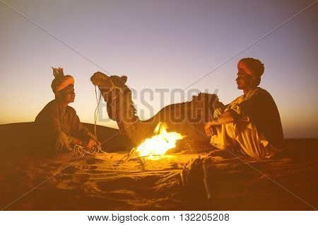 Two Indigenous Indian Men Resting By The Bon Fire Camel Concept